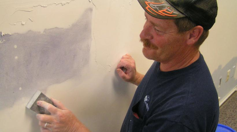 Craftsman and KU employee smooths a wall for painting.